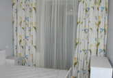 gaiši guļamistabas aizkari ar krāsainām puķēm